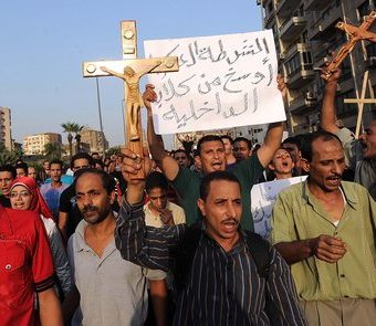 epa02961049 Egyptian Coptic Christians hold crosses and shout slogans following the death of protesters killed during clashes the day before, in Cairo, Egypt, 10 October 2011. According to media sources, thousands of protesters gathered on 10 October in central Cairo outside the Coptic Hospital, where they were waiting to receive the bodies of relatives killed in clashes a day earlier between mostly Coptic Christians and government troops. Twenty-six people were killed in violence between troops and demonstrators in front of the state television building late 09 October, and nearly 300 people were wounded.  EPA/MOHAMED OMAR