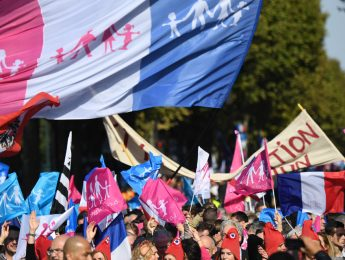 Participants wave flags and banners during a demonstration called for by the movement 'La Manif pour tous' against what are seen as 'new offensives against the family and education' in Paris on October 16, 2016.   / AFP PHOTO / Eric FEFERBERG